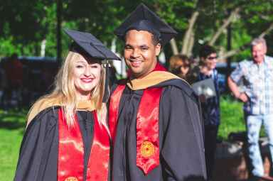 man and woman in black and red toga gown standing side by side
